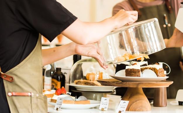 Крупным планом молодой официант, держа стеклянную крышку над тортом на стенде торт на прилавке в кафе Premium Фотографии