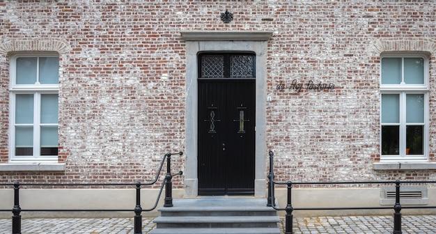 古い英語のコテージの石の壁の正面にあるヴィンテージのドアと窓。 Premium写真