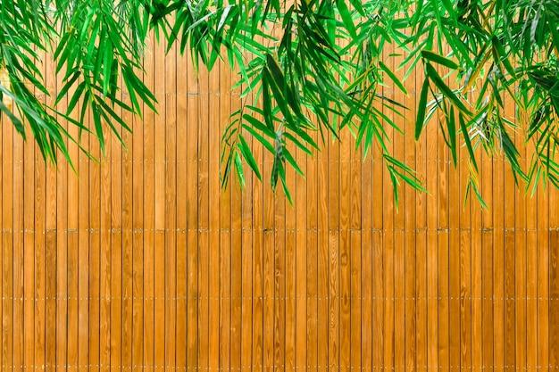 Зеленые листья бамбука и деревянные тарелки Premium Фотографии