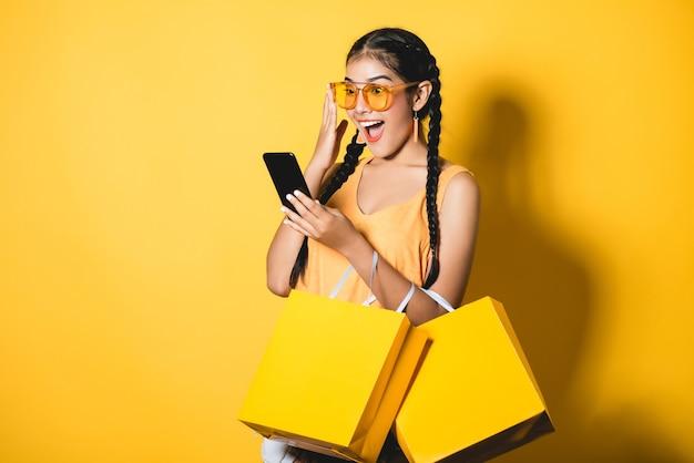 黄色の背景に彼女のスマートフォンを使用してショッピングバッグと美しい若い女性。 Premium写真