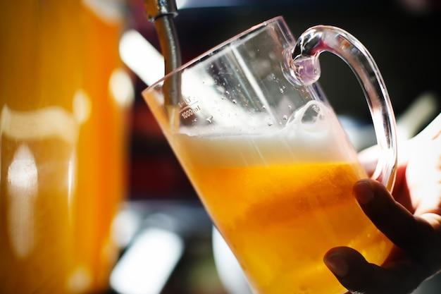 レストランやパブでドラフトラガービールを注いでビール栓でバーテンダーの手。 Premium写真