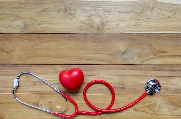 木製の背景に聴診器で赤いハート。コピースペース。心臓病。 Premium写真