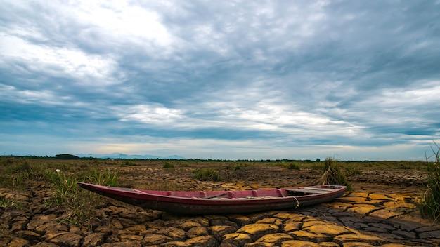 日の出と干ばつ土地の上の木造船 Premium写真