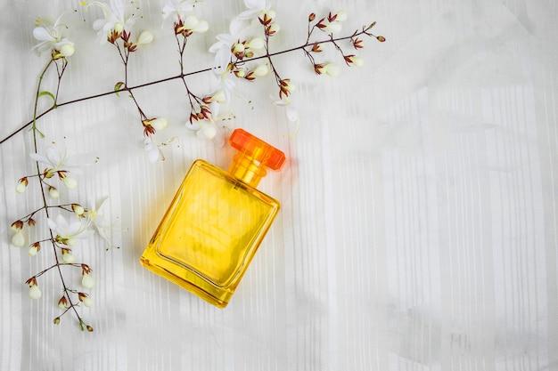 香水瓶と美しい白い背景の上の花 Premium写真