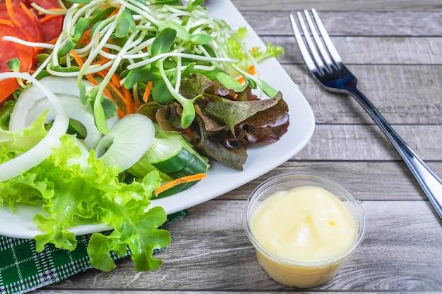新鮮なサラダとサラダドレッシング健康のために木製のテーブル Premium写真