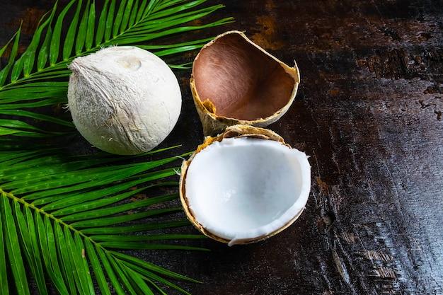 木製の背景の葉とココナッツの半分 Premium写真
