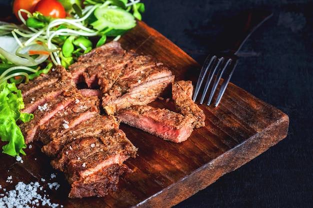 牛肉のグリルステーキとテーブルの上のヘルシーサラダ Premium写真