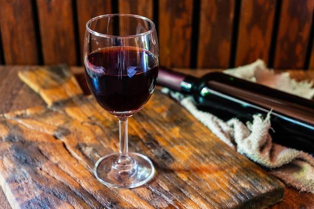 ワイングラスとワインの瓶、木製のテーブル Premium写真