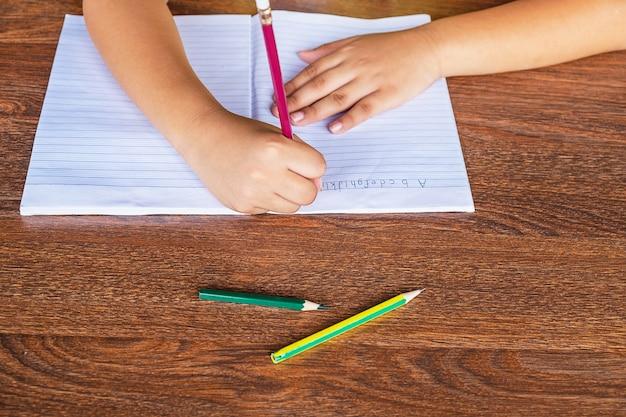生徒の手は学校のテーブルの紙に書かれています。 Premium写真