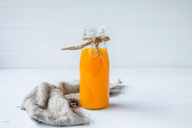 白地にオレンジジュースのボトル Premium写真