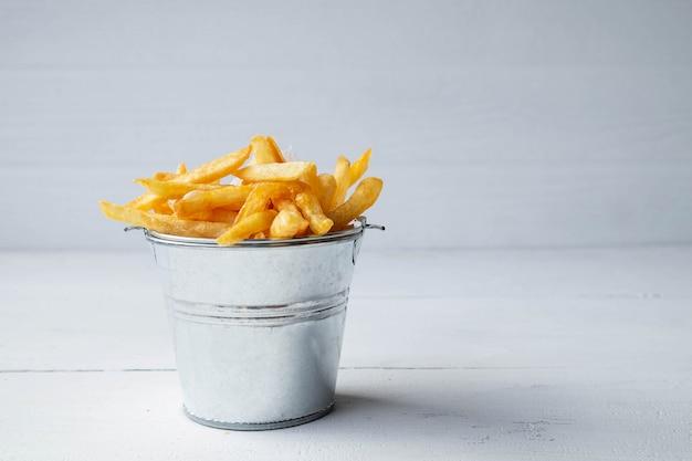 Свежий жареный картофель на белом деревянном столе Premium Фотографии