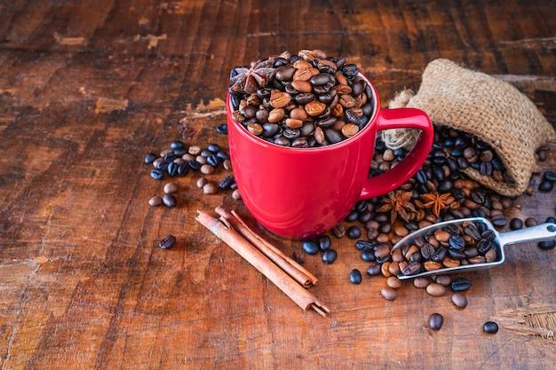 Жареные кофейные зерна в красной кофейной чашке на деревянном столе Premium Фотографии