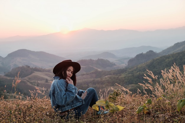 Красивая женщина сидит и наслаждается видом на горы Premium Фотографии