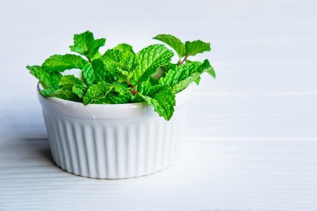 Свежие травы мяты в миску белого Premium Фотографии