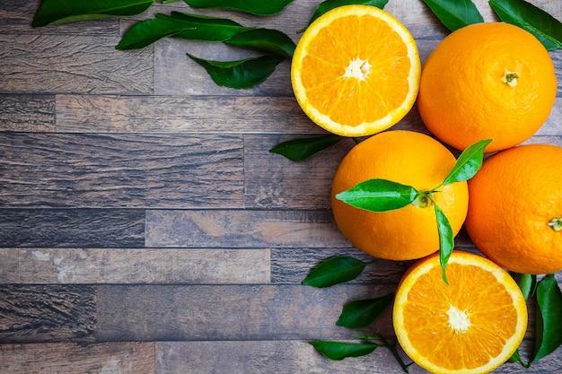 新鮮なオレンジと木の背景に葉 Premium写真