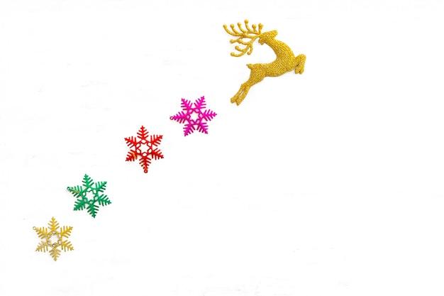 白、クリスマスツリーの装飾で隔離される美しい黄金のトナカイのおもちゃと雪の結晶 Premium写真