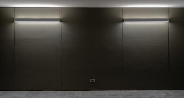 壁と床が黒い壁の背景上のランプから点灯します。 Premium写真