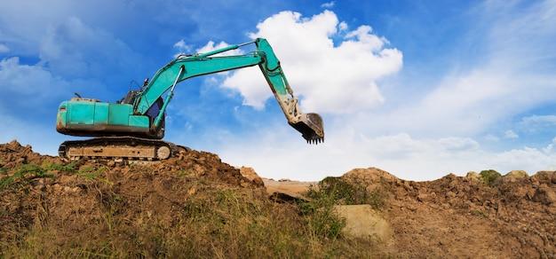 青い空の下で工事現場に取り組んでいる掘削機のパノラマ Premium写真