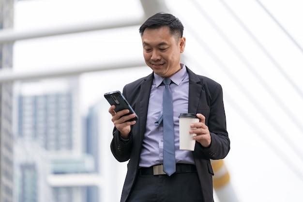 Азиатский бизнесмен стоя и держа мобильный телефон Premium Фотографии