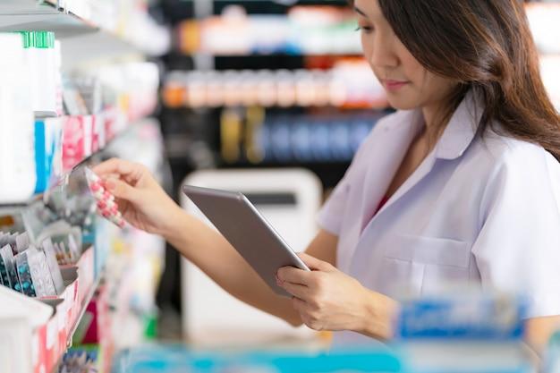 Женщина-фармацевт принимает лекарство с полки и использует в аптеке цифровой планшет Premium Фотографии