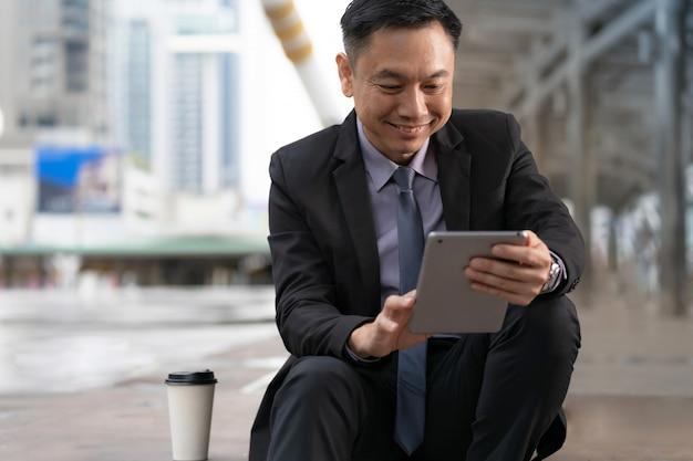 座っていると、市内のオフィスビルとデジタルタブレットを保持しているアジア系のビジネスマン Premium写真