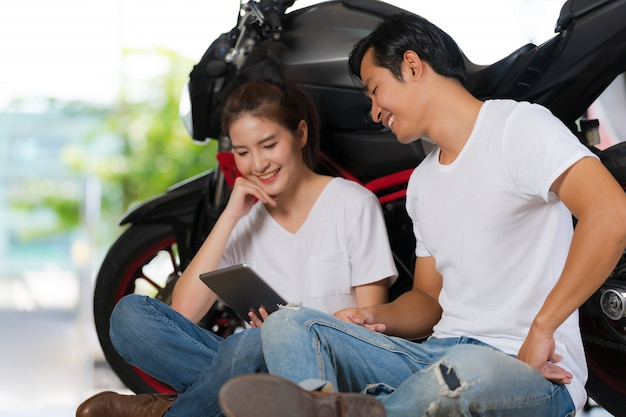 バイクの背景を持つ自宅でデジタルタブレットを使用して幸せなカップル Premium写真