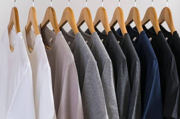 Крупным планом футболки на вешалках, одежда фон Premium Фотографии