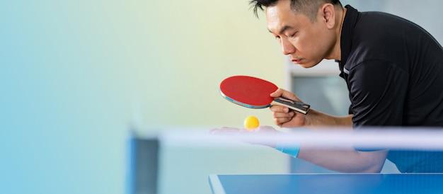 ラケットとボールスポーツホールで男性の卓球 Premium写真