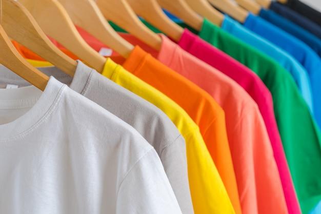 Крупным планом красочные футболки на вешалках Premium Фотографии