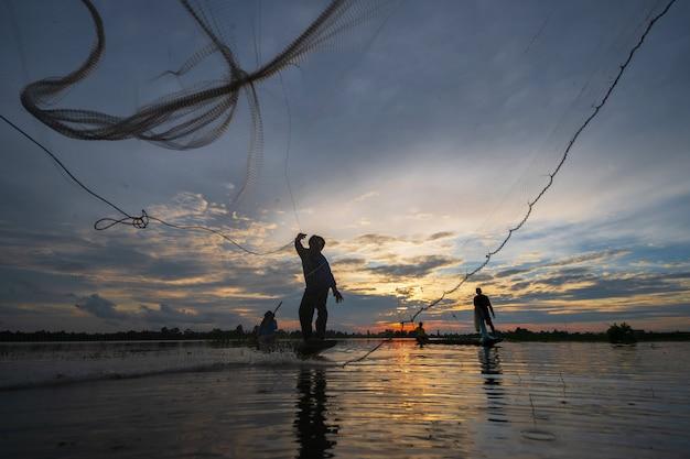 夕暮れ時、タイの湖でネットで漁船の漁師のシルエット Premium写真
