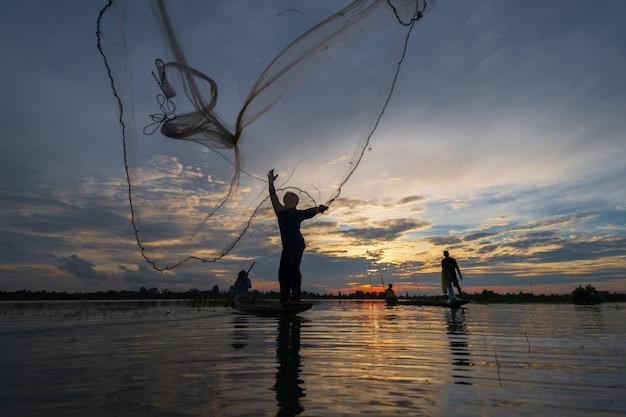 夕暮れ時の湖のネットで漁船の漁師のシルエット Premium写真