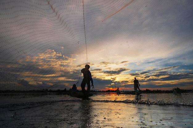 Силуэт рыбака на рыбацкой лодке с сетью на озере на закате, таиланд Premium Фотографии