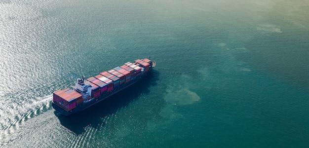 海上での輸出入ビジネスと物流における大型コンテナ貨物船の空中のトップビュー Premium写真