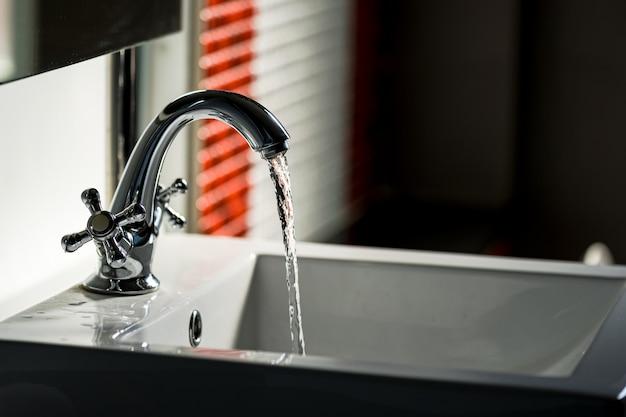 浴室の蛇口と水の流れ Premium写真