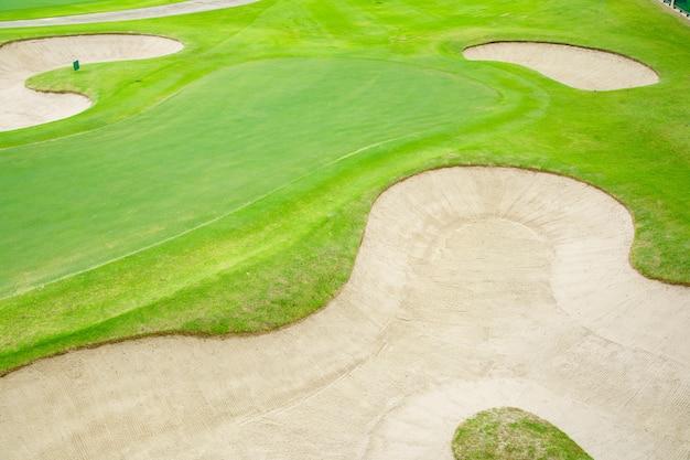 トップビューゴルフコート、美しいバンカー砂、緑と緑の自然の芝生、フェアウェイラフ。 Premium写真