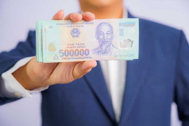 Деньги во вьетнаме держат на руках деловой человек в синем костюме Premium Фотографии