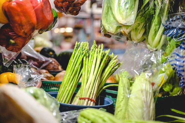新鮮なアスパラガスのオフィシナリスは、地元の市場でさまざまな野菜をテーブルに置いています。 Premium写真