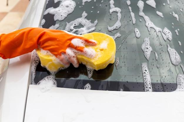 リアスポンジ現代車を洗う黄色いスポンジでオレンジ色の手袋を着ている女性の手 Premium写真