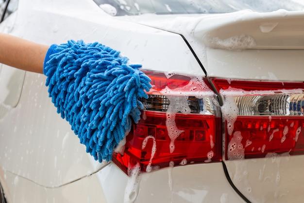 テールライト現代車を洗うか、自動車を掃除する青いマイクロファイバー生地で女性の手。 Premium写真