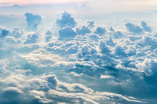 飛行機からの夕方の雲の背景と太陽の青い空 Premium写真