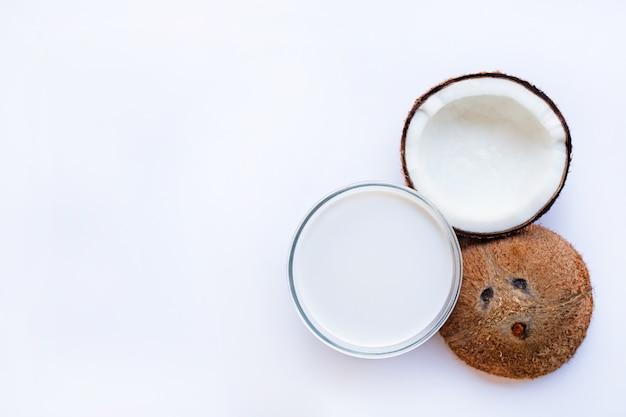 Половина кокоса со стеклянной миской с кокосовым молоком Premium Фотографии