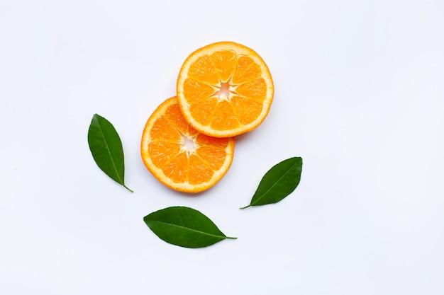 新鮮なオレンジスライス、白い背景の上の葉を持つ柑橘系の果物。 Premium写真