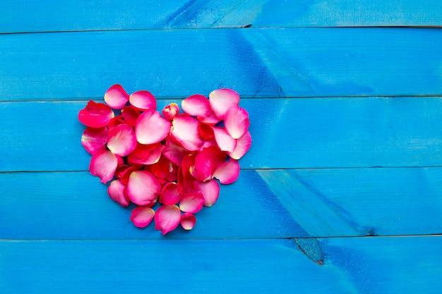 青い木製の背景にバラの花びらハート。 Premium写真