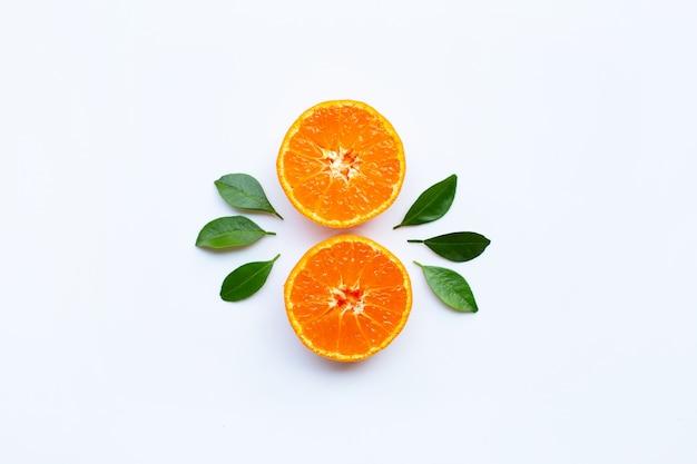 オレンジ色の果物と白い背景の上の緑の葉。 Premium写真