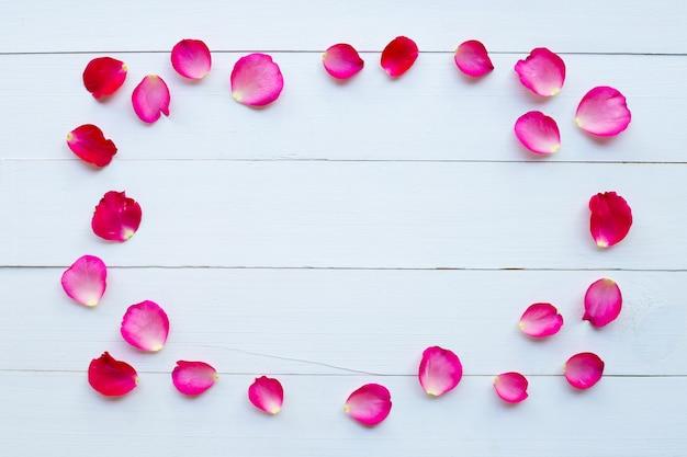 白い木製の背景にバラの花びら。 Premium写真