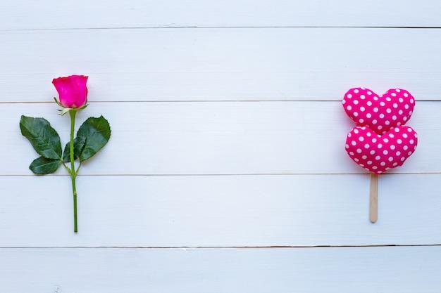 白い木製の背景にバラとバレンタインの心。 Premium写真