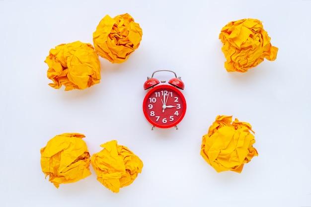白で隔離される黄色のしわくちゃの紙のボールと赤い目覚まし時計リング Premium写真