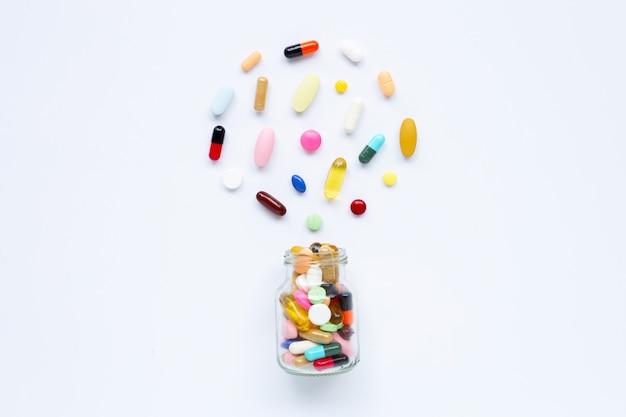カプセルと白の錠剤とカラフルな錠剤。 Premium写真