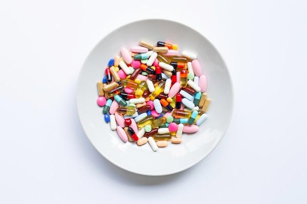 カラフルな錠剤カプセルと白の白い皿の上の丸薬 Premium写真