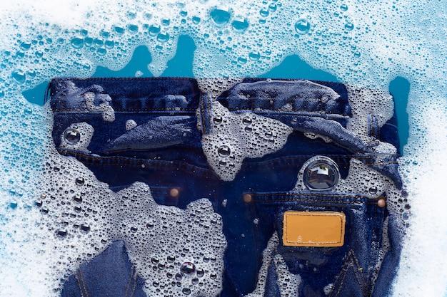 ジーンズは粉末洗剤の水に浸かる。ランドリーの概念 Premium写真